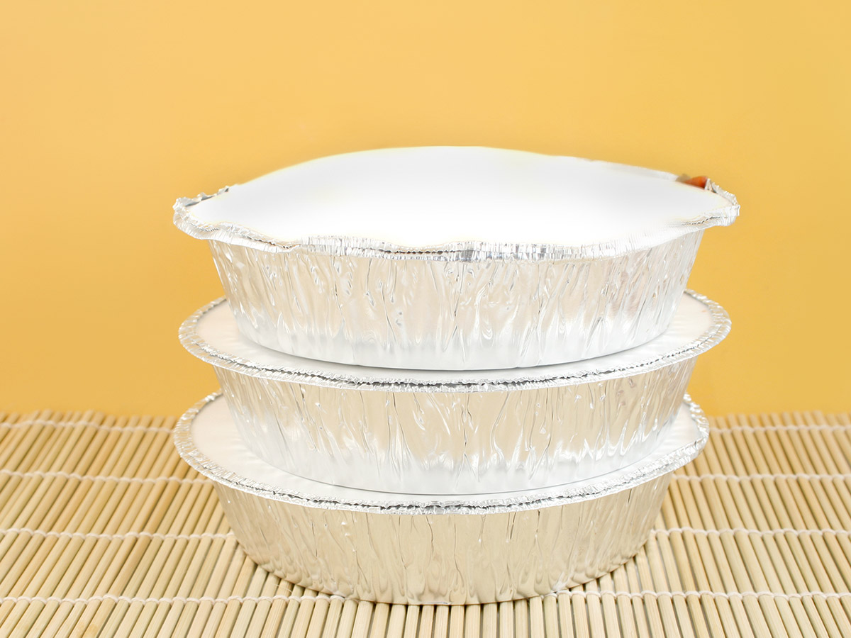 Delivery or takeout aluminum covered food containers on a bamboo placemat.