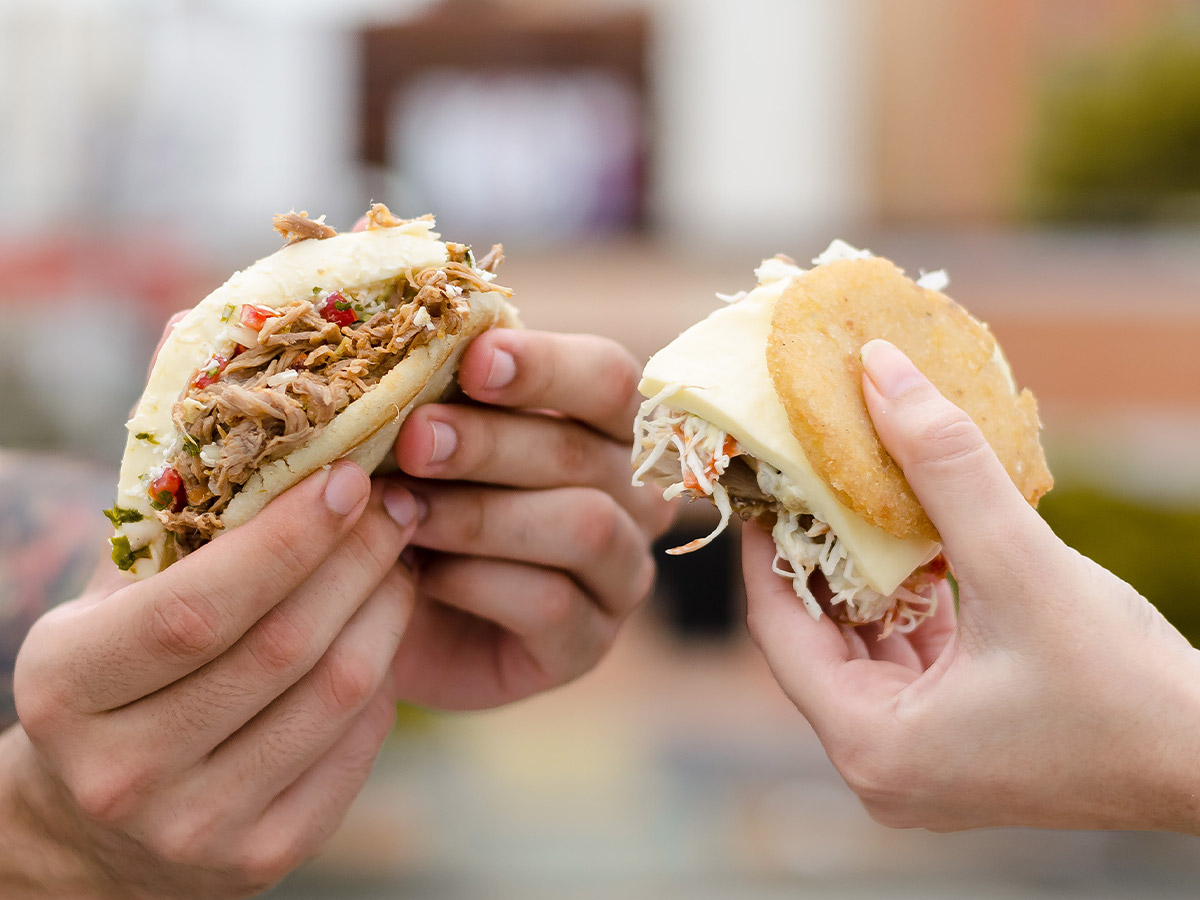 Two people holding arepas